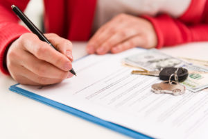 Woman auto dealer signing rental contract in the office